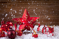 Candle,holly,baubles,star in snow Stock Photography