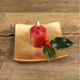 Candle and holly on old wood. Burning candle with holly on old wood as a simple Christmas theme Stock Images