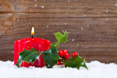 Candle and holly in snow before wooden board Royalty Free Stock Photo