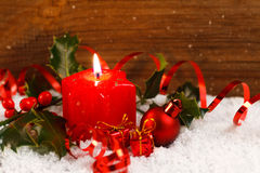 Candle and holly in snow before wooden board Stock Photography