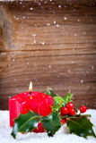 Candle and holly in snow before wooden board Royalty Free Stock Photography