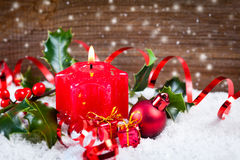 Candle and holly in snow before wooden board Stock Image