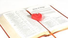 Candle on the Holy Bible. Red heart-shaped candle on pages of the Song of Songs in the Bible Stock Images