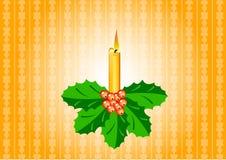 Candle with ilex. Orange candle with ilix on the orange background Stock Photo