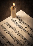 Candle illuminates the music paper Stock Image