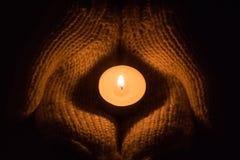 Candle a incandescência clara nas mãos do ` s da mulher Rezando, fé, conceito da religião foto de stock