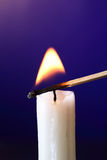 Candle Inflamed With Match. Closeup of candle inflamed with match on dark background Royalty Free Stock Photo