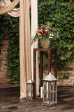 Candle lamp with a bouquet of red and white flowers. Rustic Stock Photos