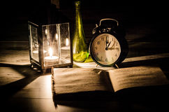 Candle Lamp Green Bottle Black Alarm Clock and Book Royalty Free Stock Images
