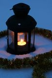 Candle lamp in snow at dusk Stock Images