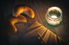 Candle lantern, notebook and croissants Royalty Free Stock Photos
