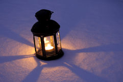 Candle Lantern in Snow. Old lantern with candle on snow at night Stock Image