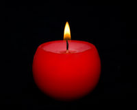 Candle light. Red round candle burning, isolated on black background Royalty Free Stock Photos