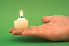 Candle light. Hand holding a candle (green background Stock Images