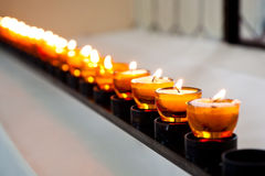 Candle light. Row of burning candles in the church Stock Images