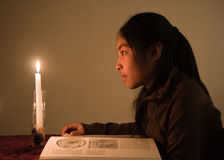 Candle light. Young girl mesmerized by the flame of a candle Stock Photos