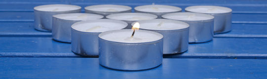 Candle light. Arrangement of tea lights with a burning one at the front Stock Photo