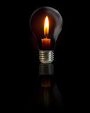 Candle on light bulb. On black background Royalty Free Stock Images