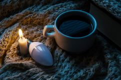 A candle, a light bulb, a cup of coffee on a scarf stock image