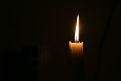 Candle light burning in dark room Royalty Free Stock Image