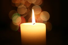 Candle light at Christmas. A lovely photo of a candle and Christmas lights behind stock photo