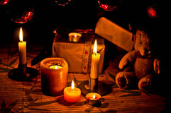 Candle light in Christmas atmosphere. Christmas atmosphere in candle-light with teddy-bear, candles, globes and christmas tree Royalty Free Stock Image
