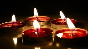 Candle light in dark background. Flat Candles on wooden board stock video footage