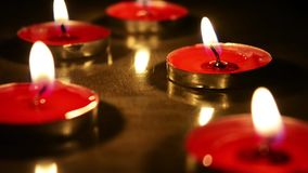 Candle light in dark background. Flat Candles on wooden board stock video