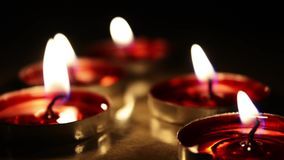 Candle light in dark background. Flat Candles on wooden board stock footage