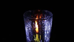Candle light with glass isolated black. Background stock video