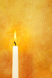 Candle light on gold. Candle flame lights hand painted gold background royalty free stock photos