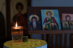 Candle light illuminating in front of orthodox saint pictures. Stock Photos