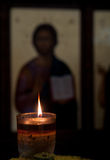 Candle light illuminating in front of the picture of the Jesus C. Hrist inside an orthodox church. Concept of religion and faith Royalty Free Stock Photography