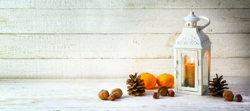 candle light lantern with pine cones, nuts and tangerines as christmas decoration on a wide, bright wooden background, panoramic stock image