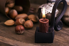 Candle Light with Nuts. Candle Light with Christmas ornament and nuts as closeup on old wood Stock Photo