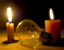 Candle light shine on incandescent bulb Royalty Free Stock Image