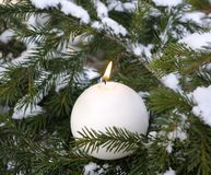 Candle light on snow-bound firry branches. Christmas view.candle in the form of a globe on snow-bound firry-tree Royalty Free Stock Image