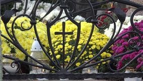 Candle light yellow chrysanthemum in metal cross in cemetery. 4K. White candle light and yellow chrysanthemum in ornamental metal cross form in cemetery. 4K stock video footage