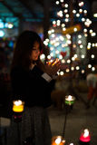 In the candle light. Young women holds a cup of candle in her hands Stock Photo