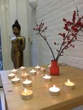 Zen. Candle lights burning with a buddha statue on a table Royalty Free Stock Image