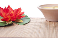 Candle and lilly on straw mat Stock Photography