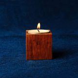 Candle that is lit on a dark blue background Stock Image