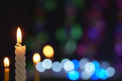 Candle lit in front of festive lights Christmas Stock Images