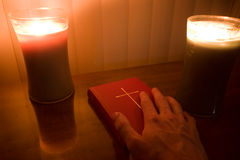 Candle lit hand on bible. Hand on Book of Common Prayer ( collection of traditional Christian Anglican liturgy) lit by candles Stock Photo