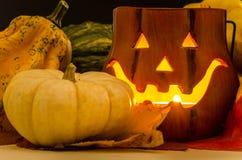 Candle Lit Jack O Lantern and Small Pumpkins Stock Image