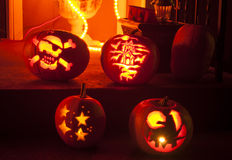 Candle lit pumpkins. 4 candle lit pumpkins sit waiting for trick or treaters Royalty Free Stock Images