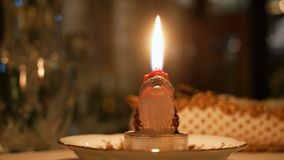 Candle lit on santa claus shape at dinner table christmas night closeup stock video footage
