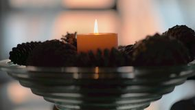 Candle lit on a tray of spinning pine cones stock video