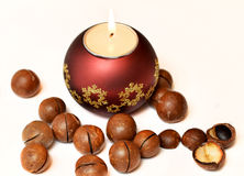 Candle and macadamia nuts Royalty Free Stock Images