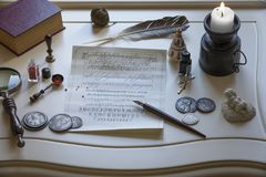 Antique writing materials and a candle on the table. Candle, magnifier, old coins and writing materials on an antique table Royalty Free Stock Images